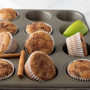 baked gluten free dairy free muffins in muffin tin with cinnamon sticks and green apple wedges