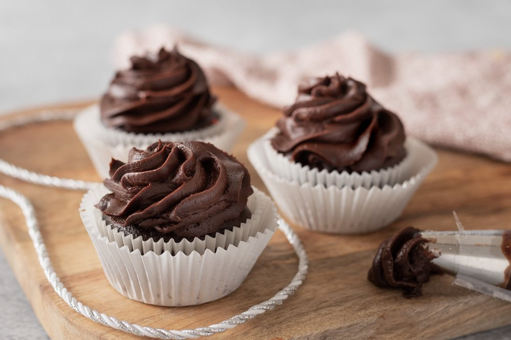 3 gluten-free chocolate cupcakes with vegan chocolate cream cheese frosting on wood board. Piping bag with frosting on right.
