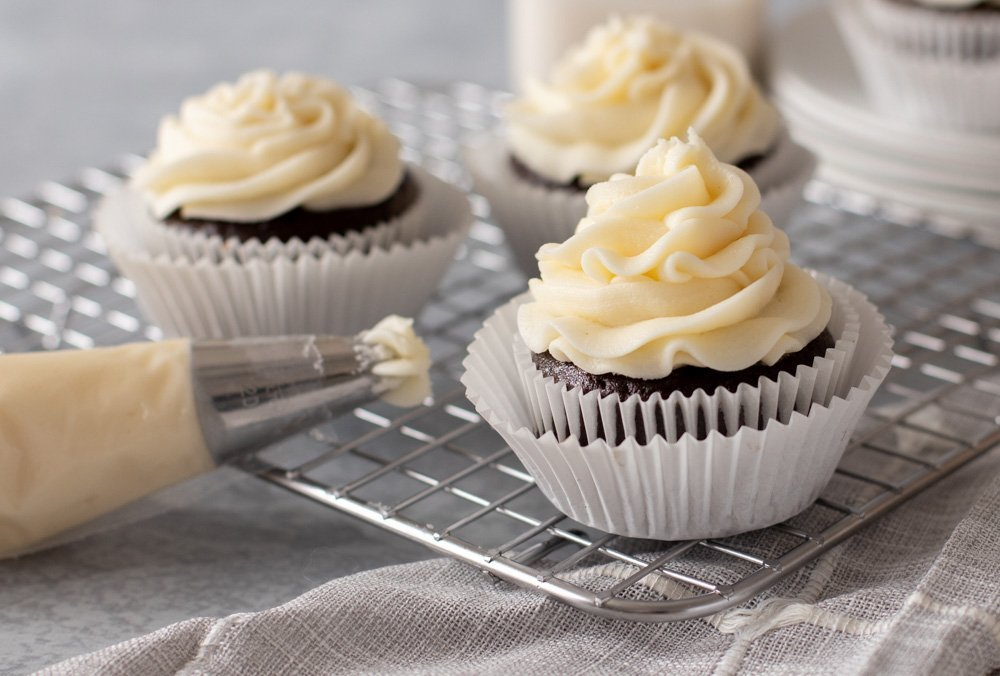 Three gluten-free chocolate cupcakes with pipeable cream cheese frosting on wire rack. Piping bag with frosting on left.