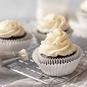 chocolate cupcakes with pipeable cream cheese frosting in cooling rack. Piping bag with frosting in front. Milk bottle in back. White background