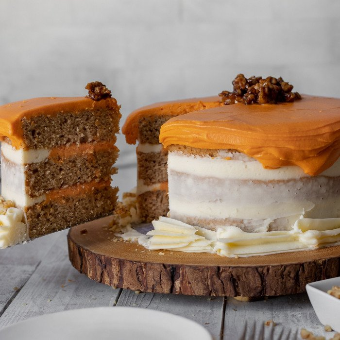 3 layer gluten-free spice cake with sweet potato frosting and cream chees frosting in wood board. Cake server removing slice from left side. Pale gray background