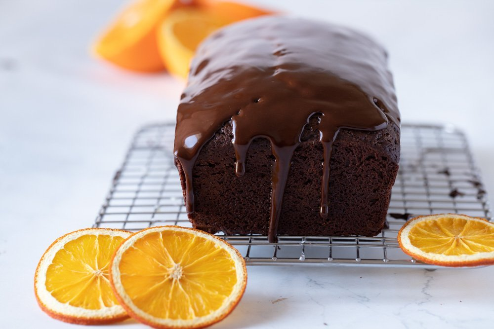 close up of chocolate orange loaf cake with chocolate ganache dripping sown sides. On wire rack with orange slices in front and back. White background