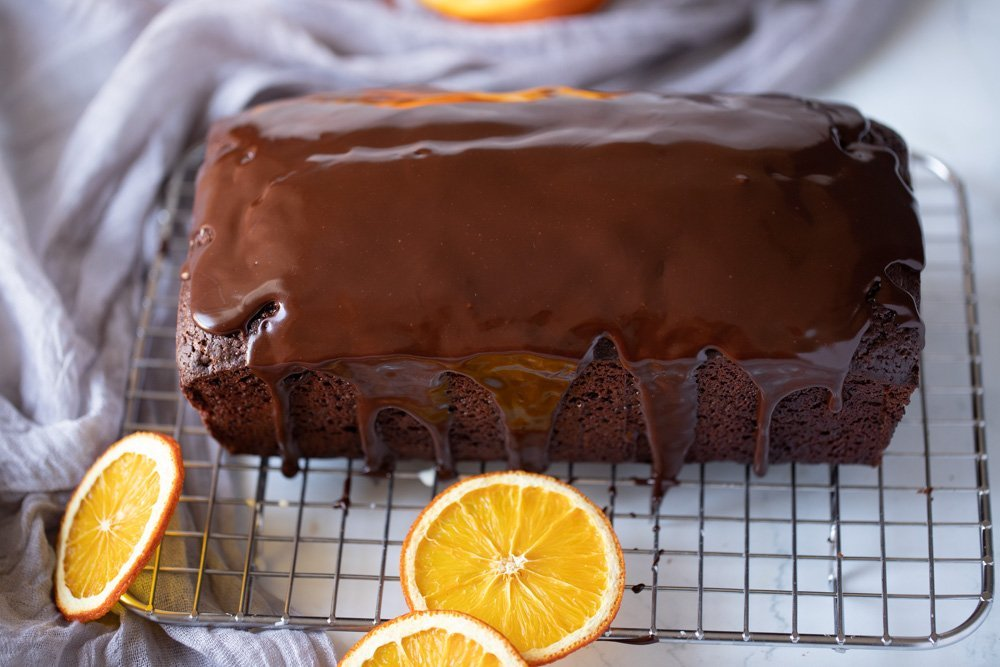 overhead view of chocolate orange loaf cake with chocolate ganache on wire rack, orange slices in foreground, background and on left