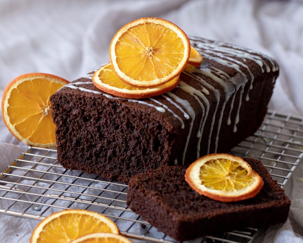 chocolate orange loaf cake with white chocolate drizzle on wire rack. Topped with dried orange slices. Slice of cake on right, Gray background.