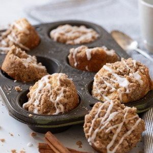 close up of gluten free coffee cake muffins in muffin tin. Cinnamon sticks in front and coffee cup with spoon on right