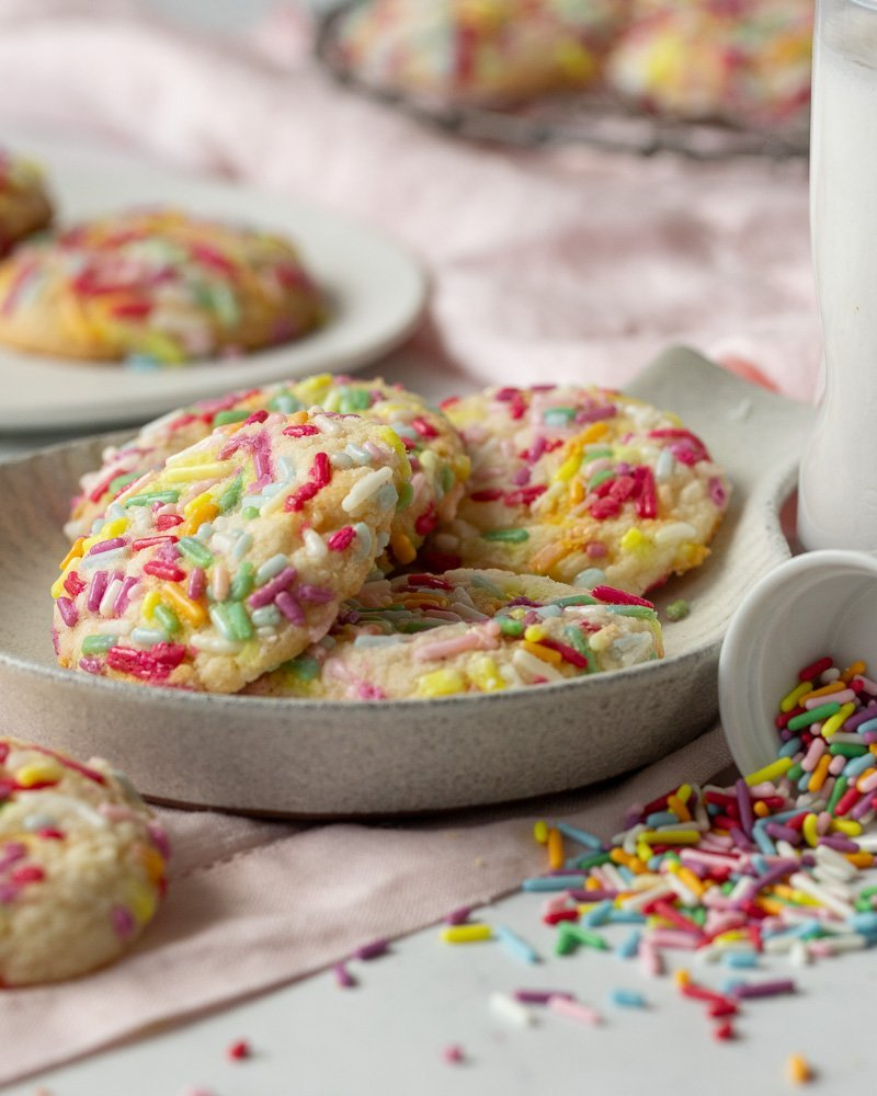 small plate with gluten free funfetti cookies. Spilled sprinkles with small bowl on right. milk glass and cooling rack with cookies in back.