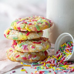 small plate with gluten free funfetti cookies. Spilled sprinkles with small bowl on right. mil glass and cooling rack with cookies in back.