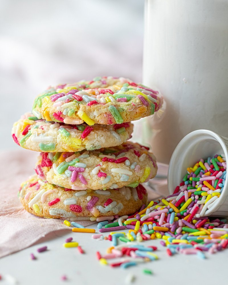 close up of stack of four gluten free funfetti cookies. Glass of milk to right and small white bowl of rainbow sprinkles tipped over in front. White background, pink napkin undrneath.