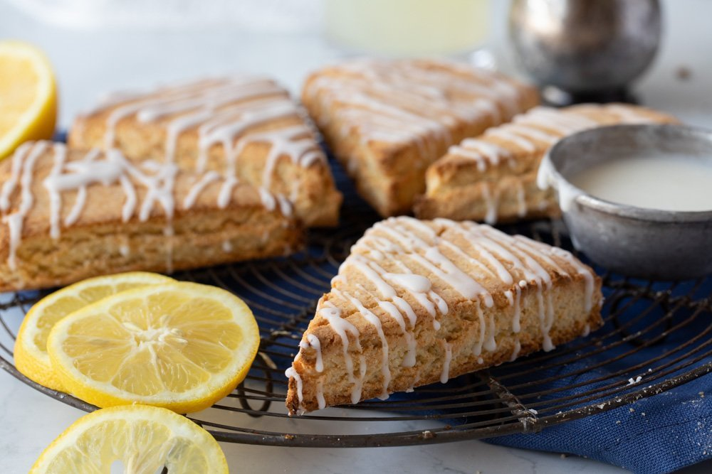 gluten free lemonade scones with lemon icing drizzle on wire rack. Metal cup with icing on right, lemon slices on left. Blue napkin underneath. Glass of lemonade in back.