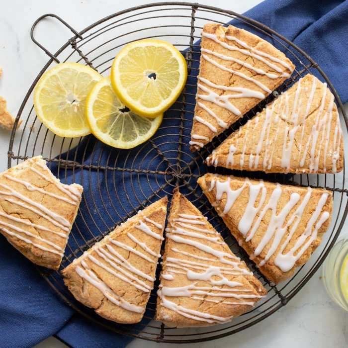 overhead view of gluten free lemonade scones with lemon icing drizzle on round wire rack with lemon slices in upper left and lemonade glass in lower right. Blue napkin underneath, white background