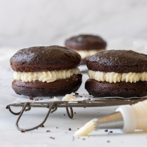close up of 2 gluten free whoopie pies on wire rack. Piping bag with frosting in front and 1 whoopie pie in far back. White marble background.