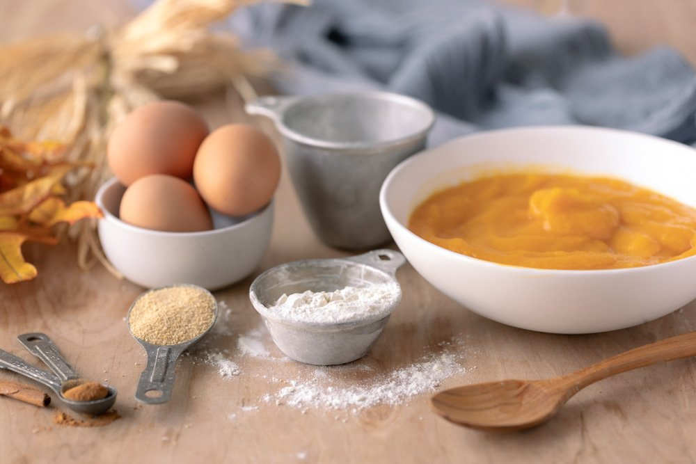 butternut squash cake ingredients - white bowl with e brown eggs, metal measuring cup with flour, measuring spoons with cinnamon and maple sugar and white bowl with butternut squash puree on right. wood spoon in front, blue napkin in background.