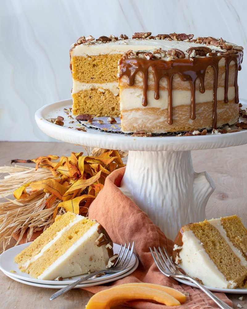 white cake stand with butternut squash cake with maple frosting. caramel drip and chooped pecans. Two slices of cake on white plates below, orange napkin, fall leaves and straw in background.