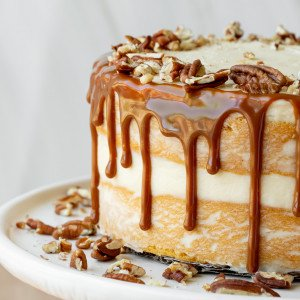 close up of gluten free butternut squash cake with caramel drip, chopped pecans on white plate