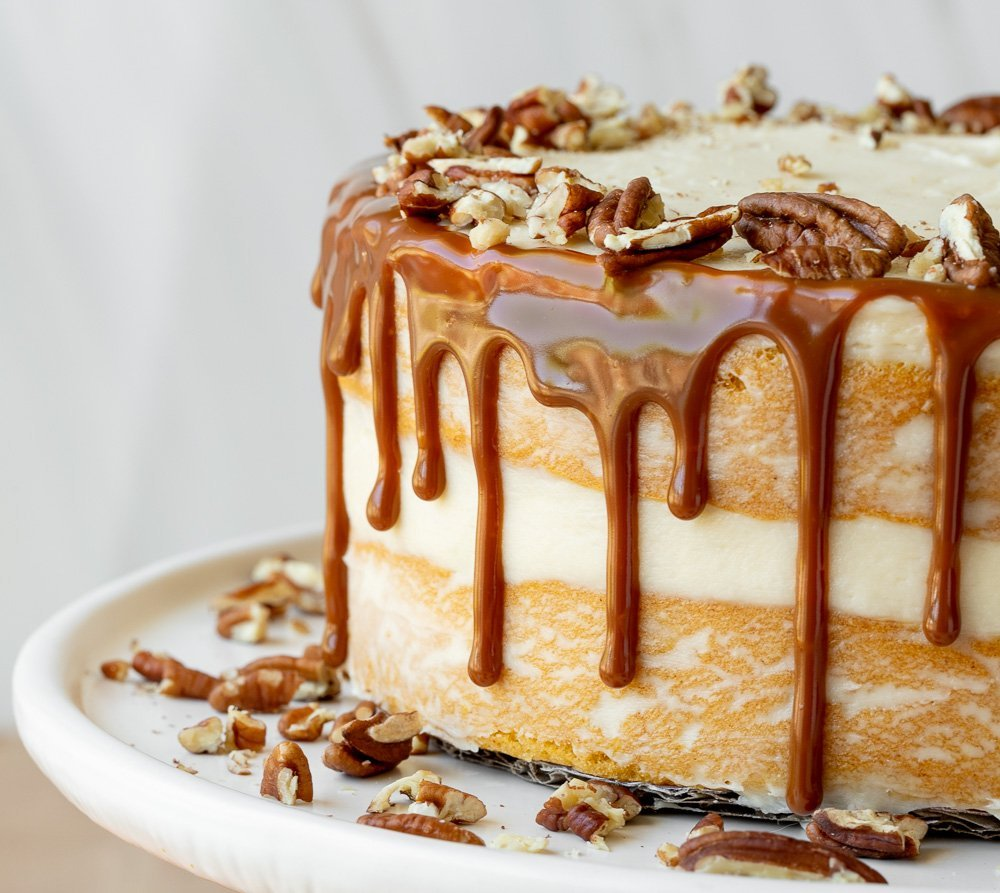 food photography close up of gluten free butternut squash cake with caramel drip, chopped pecans on white plate