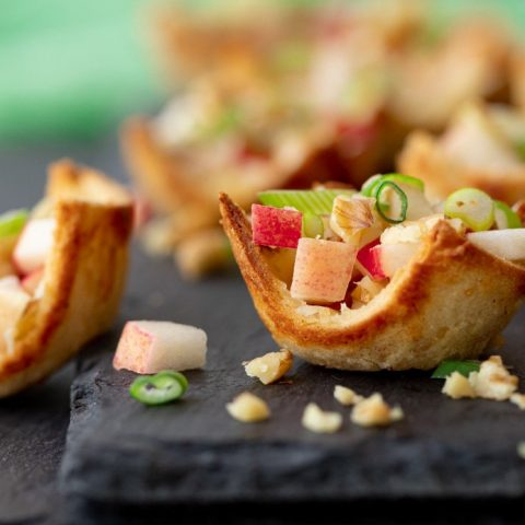 close up of gluten free tartlet appetizers with apple walnut and green onion filling on gray stone plate with green napkin in background