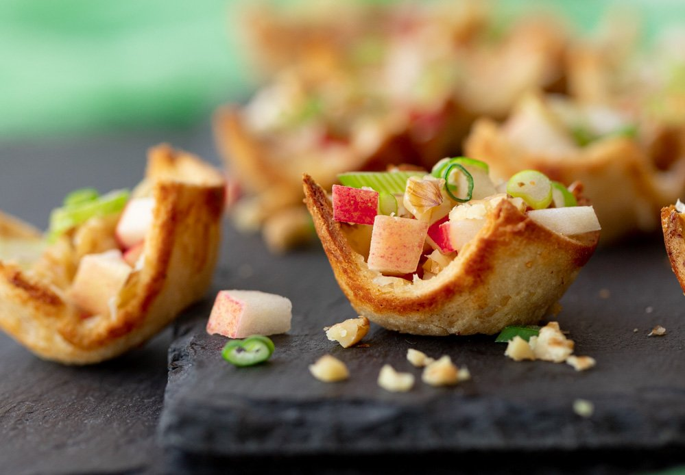 close up of gluten-free appetizer tartlets filled with apple, walnuts and green onion on gray stone plate