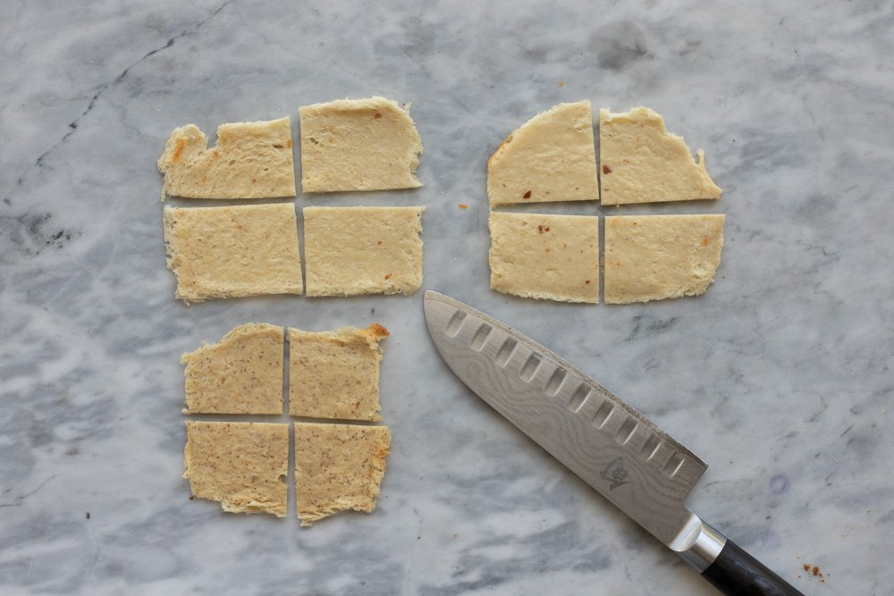 overhead view of 3 rolled out bread slices cut into 4 pieces. Knife in lower right. Marble background