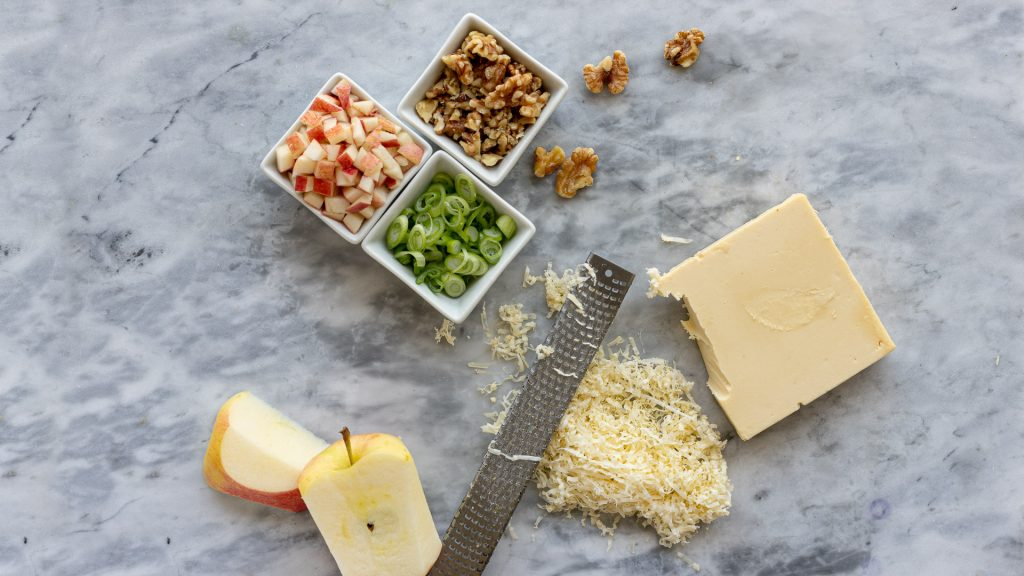 overhead view of gluten-free appetizer tartlet ingredients. Square bowls with diced apple, chopped green onion and walnuts, microplane, shredded cheese and block of vegan cheese and cut apple. Gray marble background