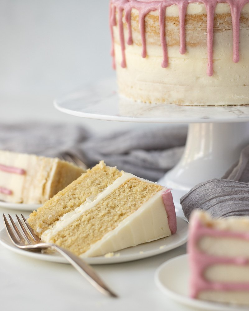 slice of 2 layer gluten free dairy free vanilla cake on white plate with fork. Whole cake on stand in background,