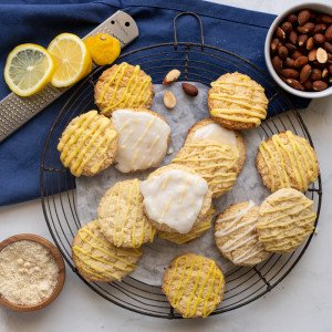 overhead view of lemon almond flour cookies on round wire rack. WHite bowl with whole almonds in upper right, wood bowl woth almond flour in lower left and microplane with sliced lemon in upper left. Blue napkin underneath