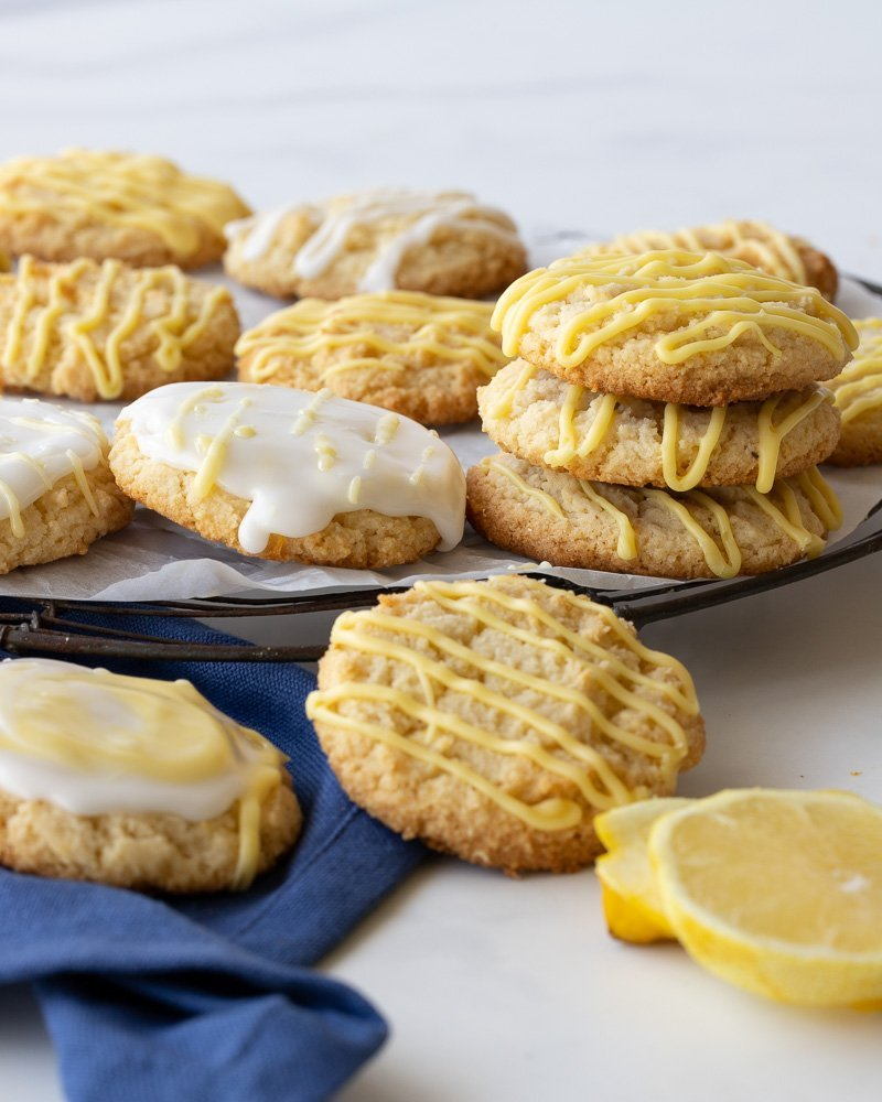 close up of lemon almond flour cookies on wire rack. Blue napkin in front left, lemon in right front.