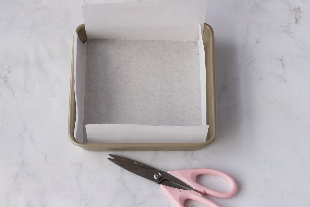 overhead view of square metal pan with parchment paper liner