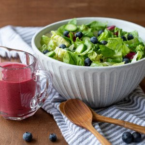large white bowl with green salad topped with cucumber and blueberries. Small glass pitcher with blueberry vinaigrette dressing on left. Two wood spoons and fresh blueberries in foreground. Gray striped napkin underneath