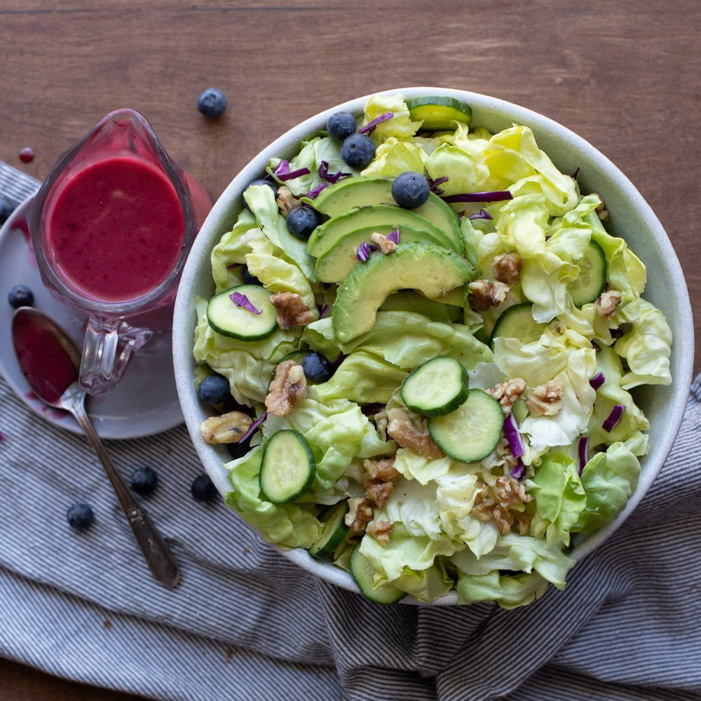 overhead view of white salad bowl with lettuce, cucumber , red cabbage, avocado, walnuts and blueberries. Small glass pitcher of blueberry vinaigrette on gray plate with spoon in upper right. Gray napkin underneath. Dark wood background.
