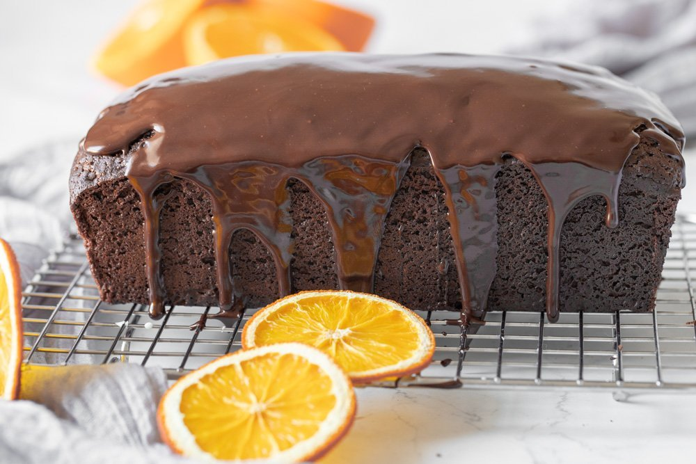 side view of chocolate orange loaf cake with chocolate ganache on wire rack, orange slices in foreground, background and on left