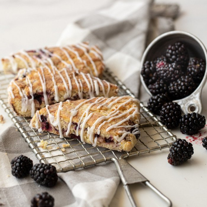 3 gluten free blackberry scones with icing drizzle on wire rack. Gray and white checked napkin underneath. Meatal bowl of blackberries tipped over.