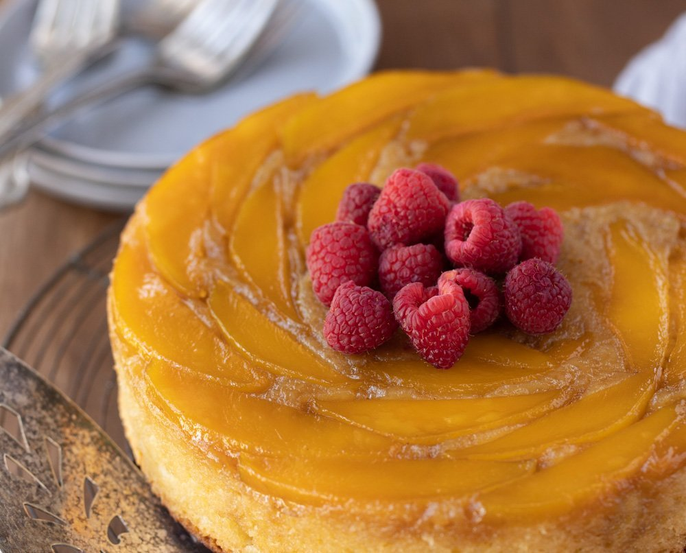overhead view of mango upside down cake topped with fresh raspberries. Cake server on left and stack of plates with forks in upper left, Dark wood background.