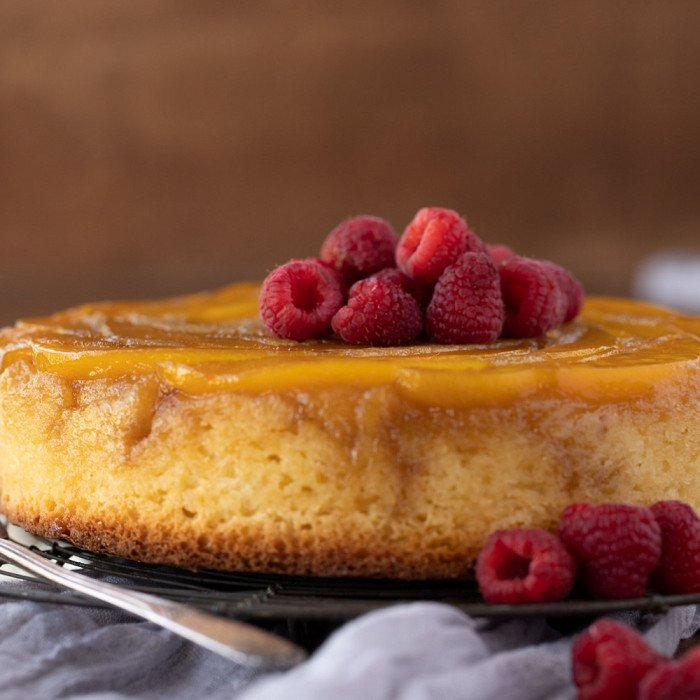 close up of mango upside down cake topped with fresh raspberries. dark wood background, gray napkin in foreground