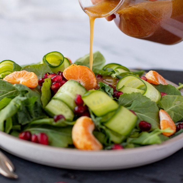 Glass carafe pouring pomegranate vinaigrette onto salad on white plate with baby arugula, tangerine sections, shaved cucumber and pomegranate seeds. Fork and spoon on left. Small salt and pepper shakers in front right. Gray slate plate underneath, white background.