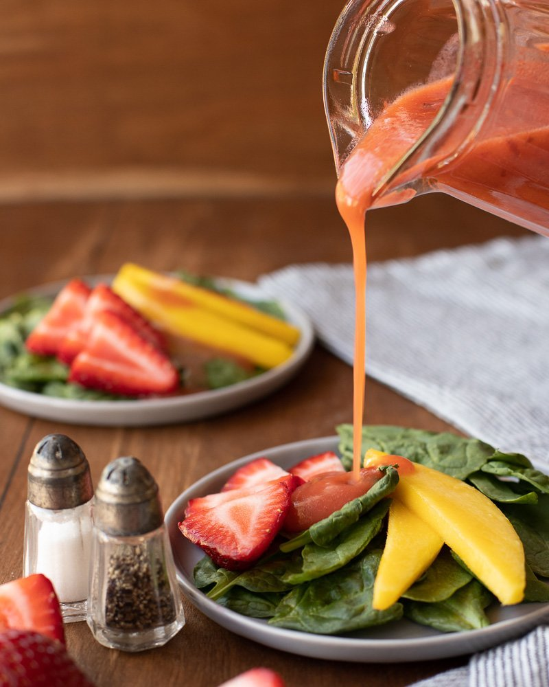 small glass pitcher pouring strawberry vinaigrette dressing onto salad with spinach, sliced strawberries and mango, Small salt and pepper shakers on left and salad plate in back. Dark wood background,