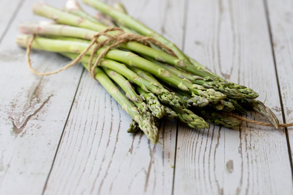 Close up of bunch of fresh asparagus tied with twine on white weathered wood surface.