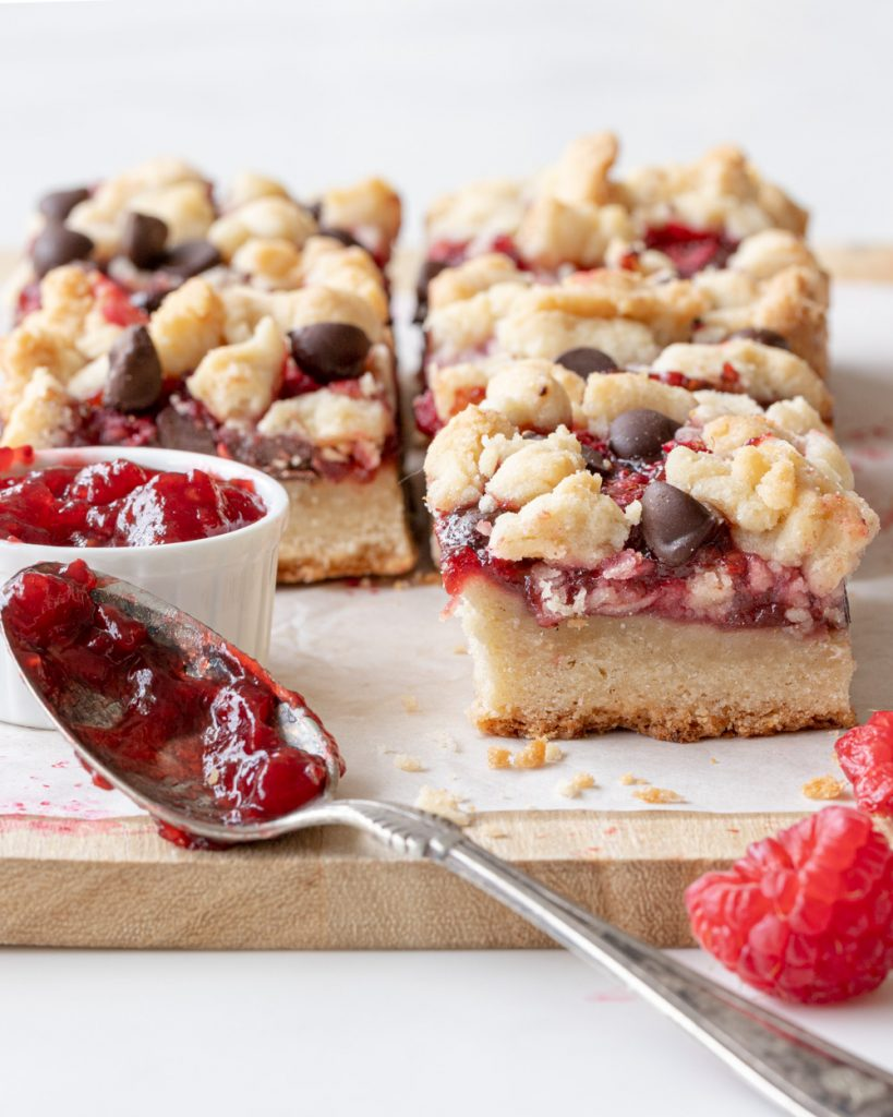 raspberry chocolate bars on parchment paper on top of wood board. Small white bowl with raspberry jam and spoon with jam in front right.