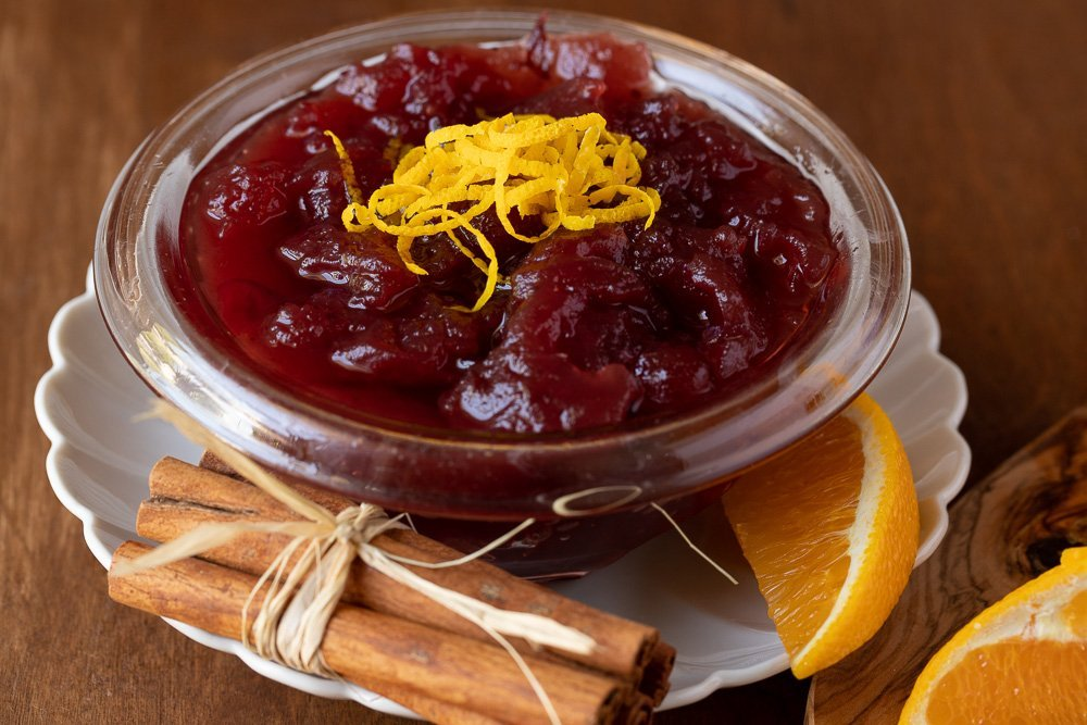 fresh cranberry sauce topped with orange zest in glass bowl with white plate underneath. Cinnamon sticks tied with straw in front, orange wedge on right.
