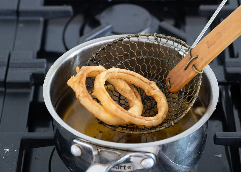 close up of frying spider removing gluten-free onion rings from pot on stove.