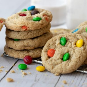wire cooling rack with stack of gluten-free m&m cookies. Cookie on right and milk bottle and glass in background