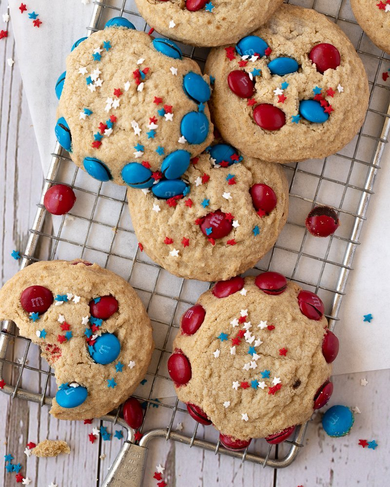 overhead view of gluten free cookies with red and blue m&m's on wire cooling rack. Crumbs and m&m's scattered around on white background