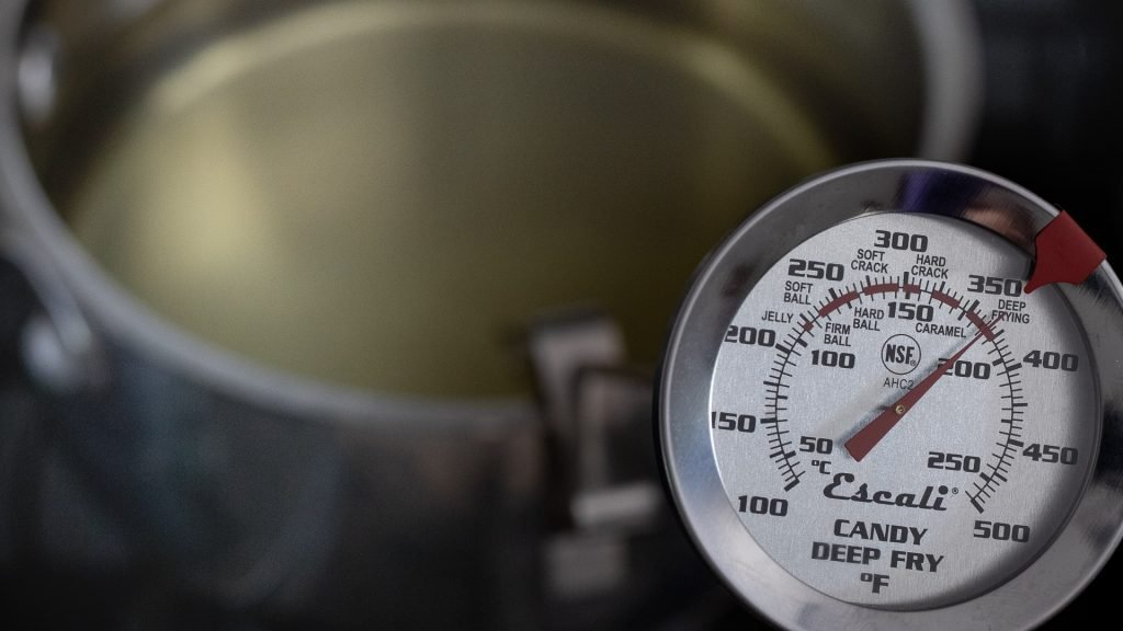 Overhead view of frying thermometer clipped to side of a pot filled with oil.