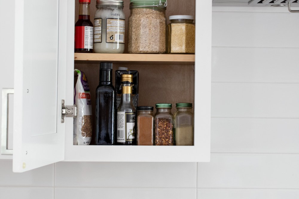 Open kitchen cabinet with spices, bottles and jars of gluten free grains