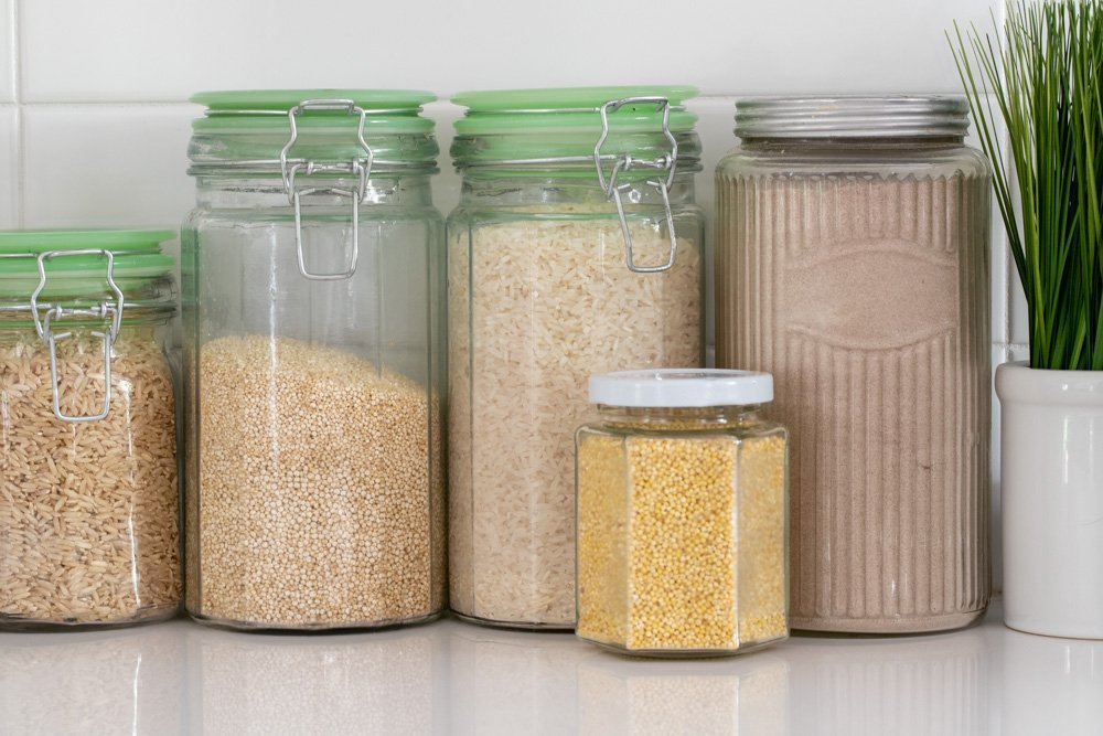 5 glass jars with rice, quinoa, millet grain and teff flour on white kitchen counter with white tile backsplash. Plant in white pot on right.