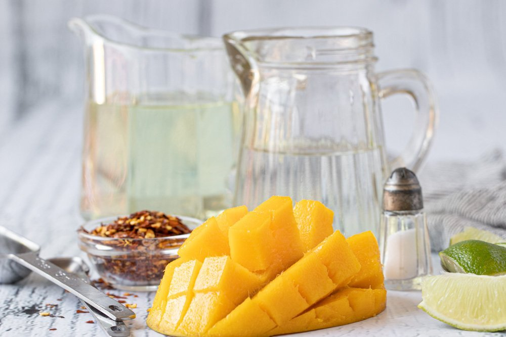 Ingredients for mango vinaigrette: Cut mango, small salt shaker and lime wedges on right. Measuring spoons and small bowl of chili flakes on left. Glass pitchers with vinegar and oil in background.