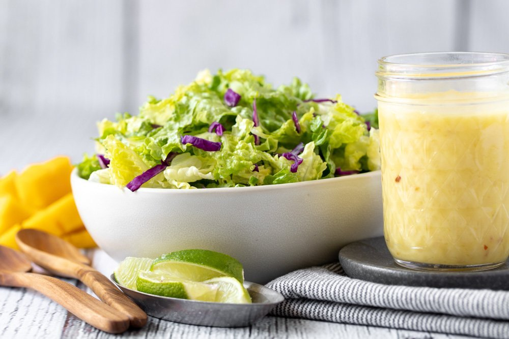 large white bowl with green salad. Jar of mango vinaigrette on right. Metal bowl with lime wedges in front. Wood spoons and cut mango on left. Gray background.