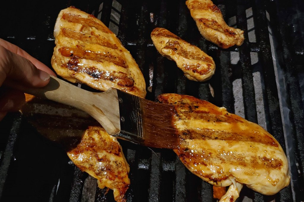chicken breasts cooking on grill. Pastry brush on left brushing marinade on chicken,