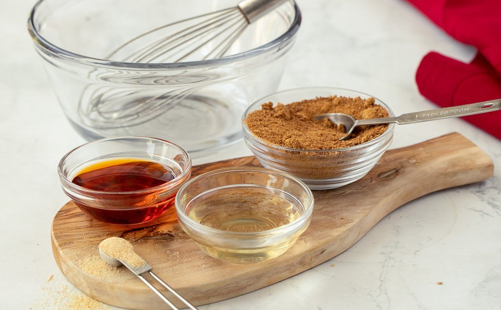 ingredients for 4 ingredient marinade for chicken including glass bowls with sesame chili oil, rice vinegar, coconut sugar and measuring spoon with onion powder, Wood board underneath, Red napkin on right and glass bowl with wire whisk in background.