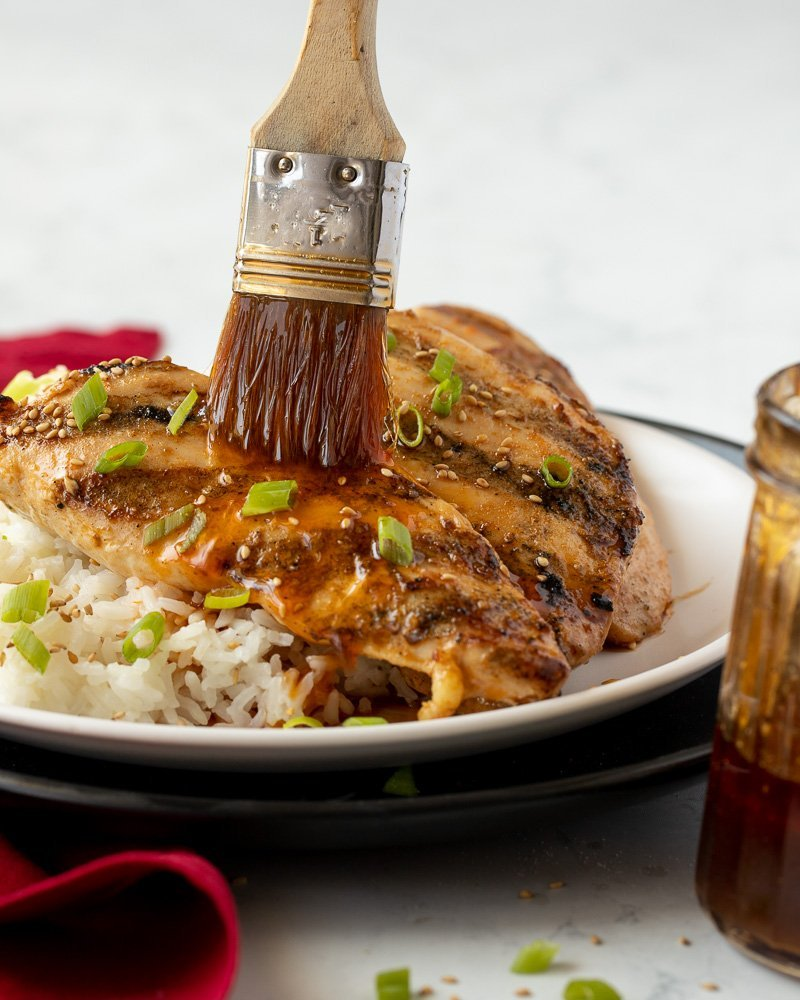 close up of grilled chicken with 4 ingredient marinade on white plate with white rice. Green onion and sesame garnish. Pastry brush brushing marinade on to chicken. Red napkin and glass pitcher with marinade in front. White background.