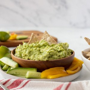Wood bowl with 4 ingredient guacamole with 2 chips dipped in. White pale underneath with sliced cucumber and red pepper. Half lime on left and wood cutting board with veggies in background